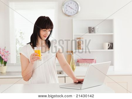 Beautiful brunette woman holding a glass of orange juice while relaxing with her laptop in the kitchen