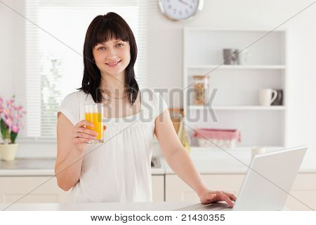 Gorgeous brunette woman holding a glass of orange juice while relaxing with her laptop in the kitchen