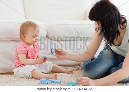 Beautiful woman and her baby playing with puzzle pieces while sitting on a carpet in the living room