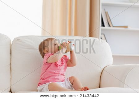 Cute blond baby bottle-feeding while sitting on a sofa in the living room