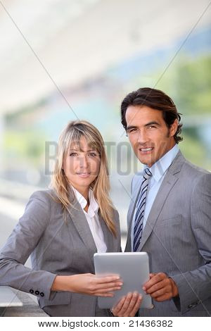 Business team using electronic tablet outside offices building