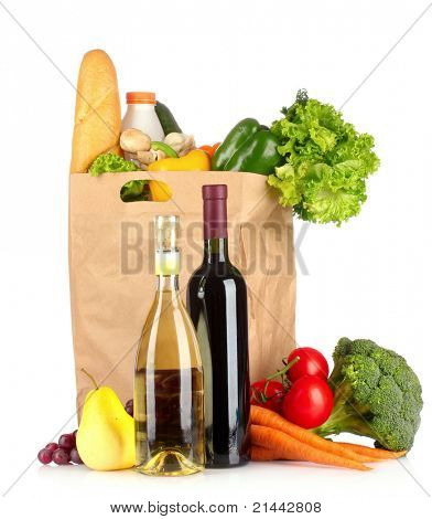 Vegetables in paper bag and wine bottles isolated on white