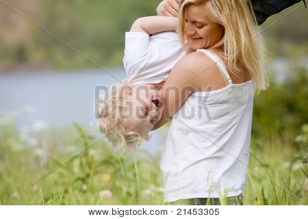 A mother tickling and playing with excited happy son in a green meadow