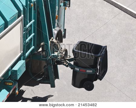 City owned trash truck lifts can with robotic arm.
