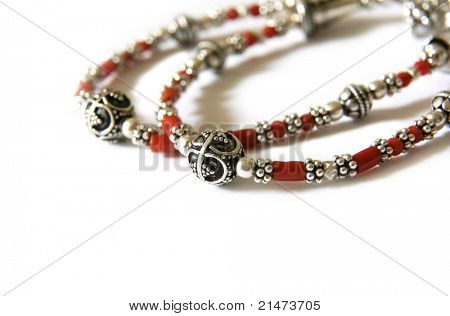 Unique bracelet made of silver and coral beads, isolated on white. Handicraft from Croatia.