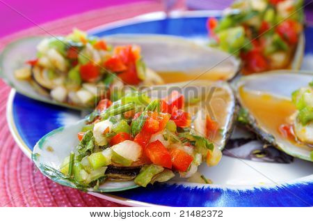 appetizer of mussels with vegetables over pink table