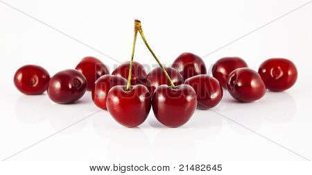 two cherries with stems in front of cherry