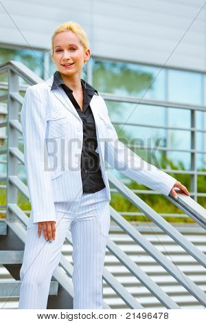 Smiling modern business woman standing on stairs at office building and holding hand on railing
