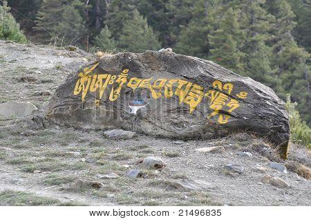 Pointer carved into a stone to Milerepa Monastery