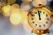 new Years at midnight - clock at twelve oclock with holiday lights poster