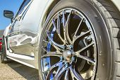 Close Up Of A Cars Rim, Wheel With No Emblem Chrome Rims And Blue Bolts On A White Car poster