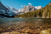 The Loch Lake with rocks and mountains in snow around at autumn. Rocky Mountain National Park in Col poster