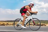 Triathlon cyclist man cycling racing on road bike on ironman competition racing against time. Triath poster