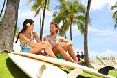 Hawaii surfers people lifestyle happy living couple talking on Waikiki beach relaxing from surfingwi poster