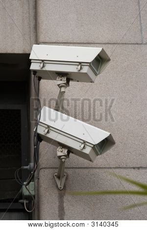 Pair Of Security Cameras Mounted To Building
