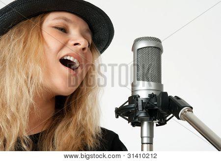 Junge Frau mit Studiomikrofon singen