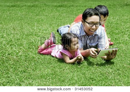 Happy Father And Children Outdoor With Digital Tablet