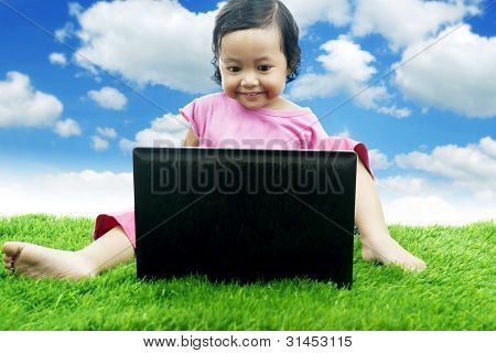 Cute Asian Girl Sitting On Grass With Laptop
