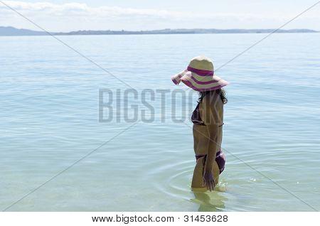 woman walking in the sea wearing hat.