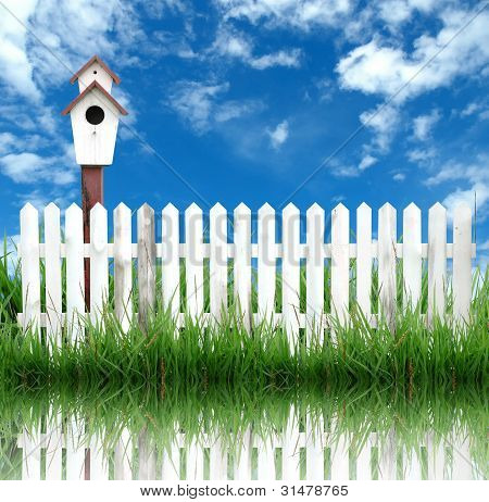 weißen Zaun mit Vogelhaus und blauer Himmel