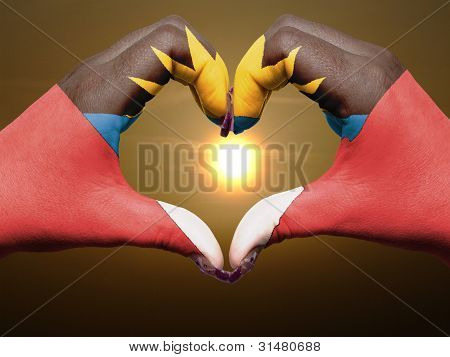 Heart And Love Gesture By Hands Colored In Antigua Barbuda Flag During Beautiful Sunrise For Tourism