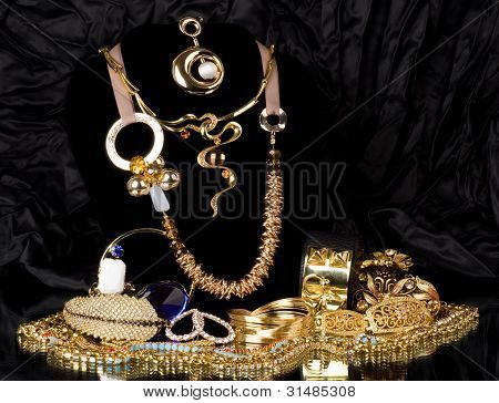 Gold jewelry (rings,bracelets and necklaces)on a black background