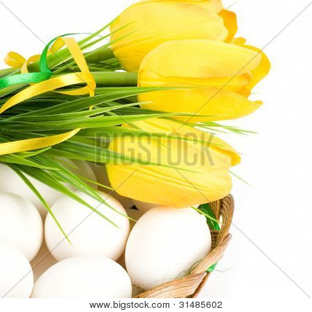 Basket with Easter eggs and spring tulips on white background