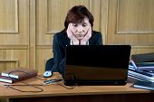 pic of average looking  - business woman thoughtfully looks at the laptop in an office - JPG
