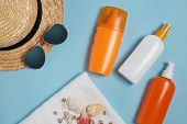 Sun Cream, Sun Hat, Cream, Sunscreen Bottle, Sun Cream, Lotion Bottle, Seashells On A Blue Backgroun poster