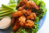 stock photo of fried chicken  - buffalo chicken wings with celery sticks on plate - JPG