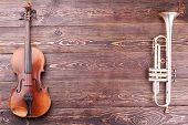 Violin, Trumpet And Copy Space. Musical Instruments Of Orchestra On Textured Wooden Background With  poster