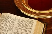 stock photo of tithe  - Close up of part a page of a pulpit Bible next to a church collection plate - JPG