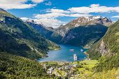 Norway Cruise, Mountains And Village In Geiranger Fjord. poster