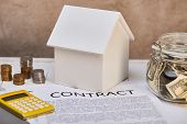 House Model, Coins, Yellow Calculator Near Contract And Moneybox, Real Estate Concept poster