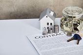 House Model On White Table With Silver Coins, Keys, Contract And Moneybox, Real Estate Concept poster