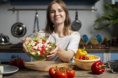 Young Cheerful Girl Prepares A Vegetarian Salad In The Kitchen, Holds A Ready Meal In Her Hands, The poster