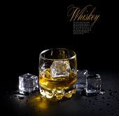 image of malt  - glass of whiskey and ice over a black background - JPG