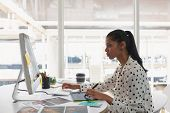 Side view of beautiful mixed-race female graphic designer using graphic tablet at desk in office. Mo poster