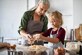 Cute girl learning preparing dough with mature grandmother in kitchen. Lovely old grandma and grandd poster