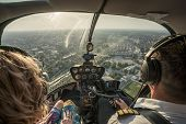 Portrait Of Beautiful Blonde Women And Pilot Enjoying Helicopter Flight. She Is Amazed By Cityscape. poster