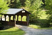 stock photo of dirt road  - A covered bridge in the country on a sunny morning - JPG
