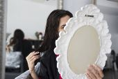 Woman Looking At Her Hair With A Mirror In A Hair Salon poster