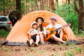 Happy Family Camping In Forest, Playing Guitar And Singing Song Together In Front Of Tent. Concept O poster