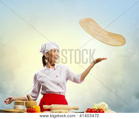 Asian female cook making  pizza