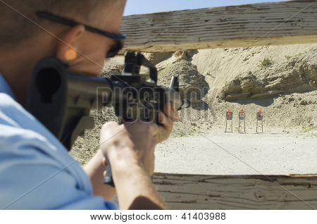 Rear view of man aiming target with gun
