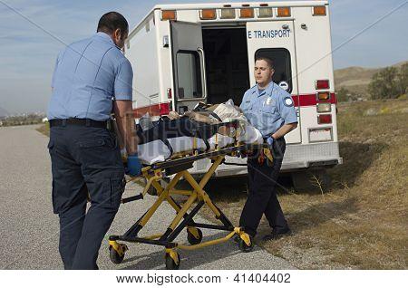 Male paramedics carrying patient on stretcher to the car