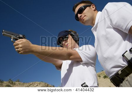 Trainer helping young woman to aim with handgun at combat training