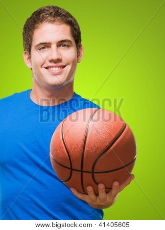 Happy young man holding a basketball against a green background