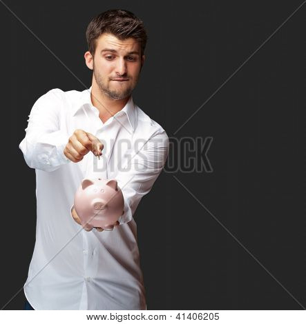 A Businessman Putting A Coin Into A Pink Piggy Bank Isolated On Black Background