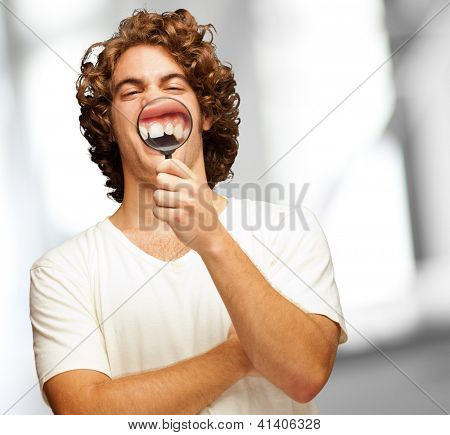 Man Examining His Teeth With Magnifier, Indoor
